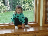 This is a picture of me sitting on the ledge in the sunroom when I was barely 2 years old.